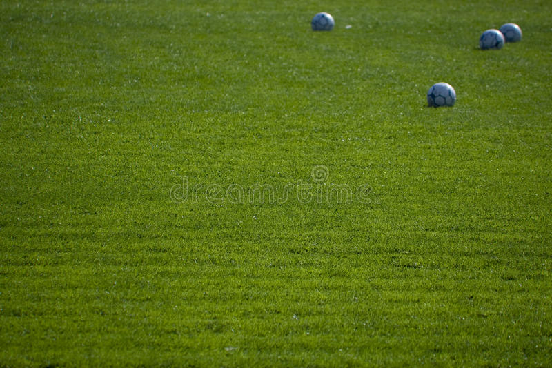 Green empty football ground with balls. (focus on a grass stock images