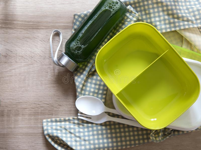 Green empty lunch box wrapped on wooden table , top view or overhead shot , green food concept. The green empty lunch box wrapped on wooden table , top view or stock photo