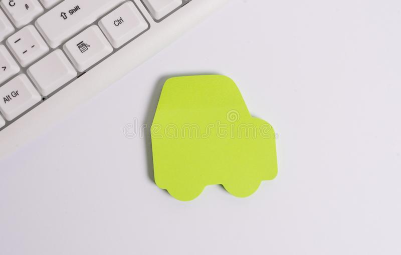 Green empty note paper in the shape of the car. Copy space on the green note paper. Pc keyboard with blank note paper. Green empty note paper in the shape of the stock photos