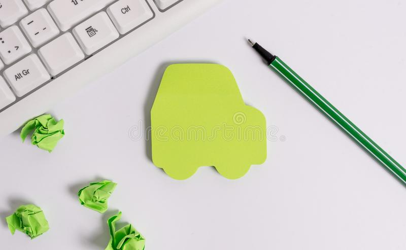 Green empty note paper in the shape of the car. Copy space on the green note paper. Pc keyboard with blank note paper. Green empty note paper in the shape of the stock photography