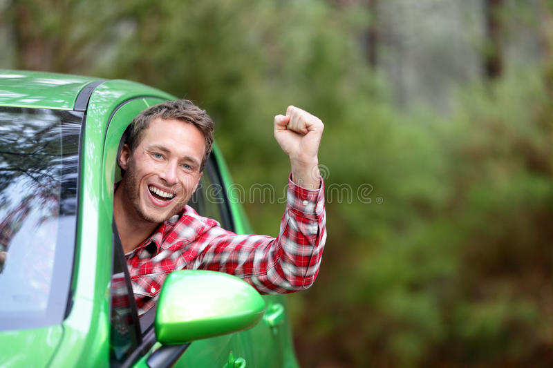 Green energy biofuel electric car driver happy. And excited. Man driving new vehicle in cheerful in nature forest. Young male driver looking at camera with arm stock photo
