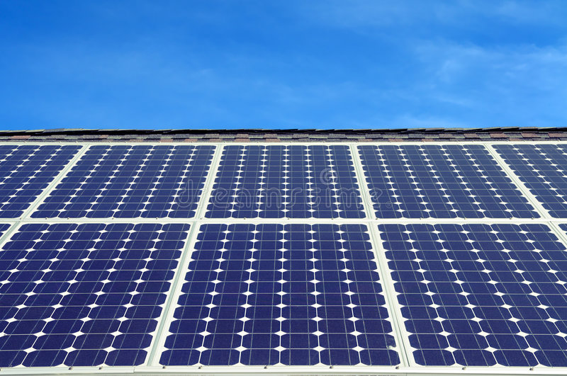 Green energy, blue background. Blue solar panels on the roof of a house royalty free stock photos