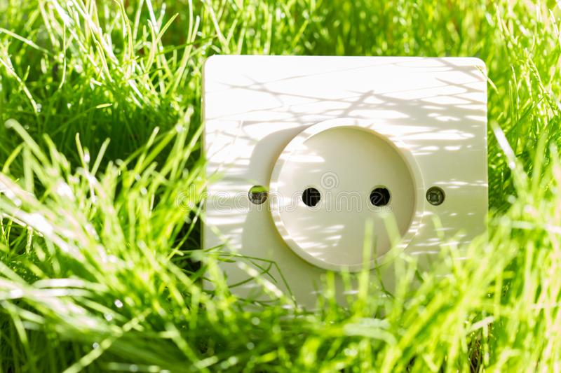 Green energy concept with socket in the grass outdoor. Closeup royalty free stock photos