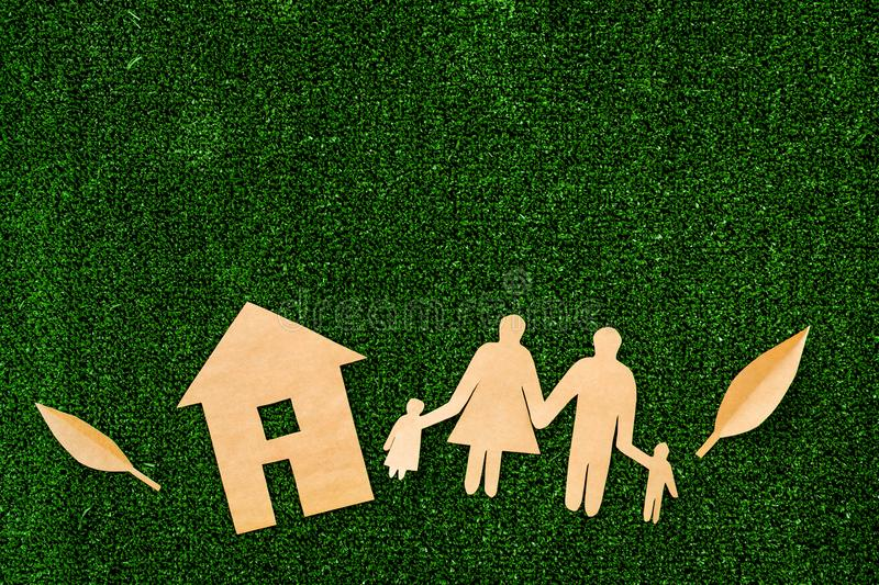 Green energy for home concept. Care for environment. House cutout made of craft paper near family cutout on green grass stock photo
