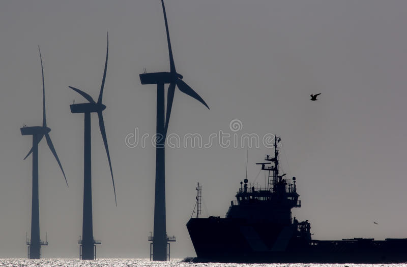Green energy. Offshore wind farm turbines with ship at sea. Silhouette at dawn. stock image
