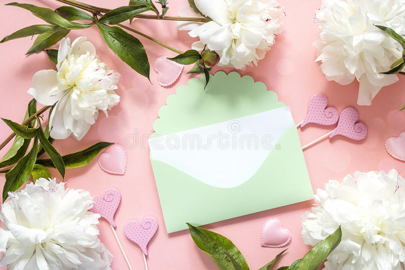 Green envelope with white peonies and decorative hearts on a pin royalty free stock image
