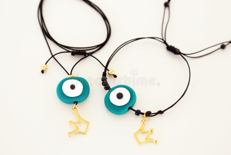 Green evil eye jewelry necklace and bracelet set with golden crown stock image
