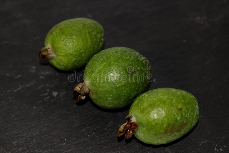 Green exotic fruits feijoa on a black background stock photography
