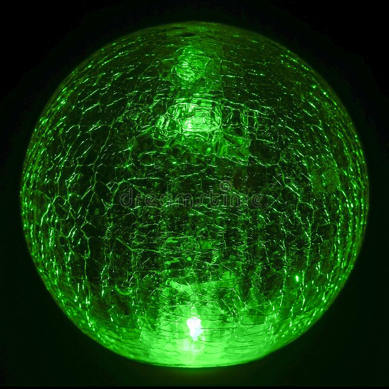 Green exterior light powered by the sun. Exterior green night light sphere in a garden powered by the sun for saving energy royalty free stock image