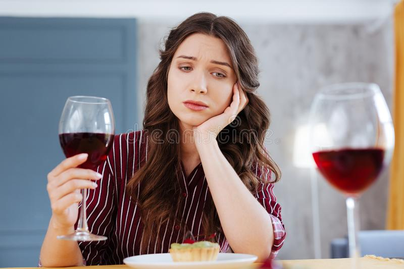 Green-eyed woman being left alone on Friday night. Left alone. Green-eyed beautiful woman feeling extremely depressed while being left alone on Friday night stock photo