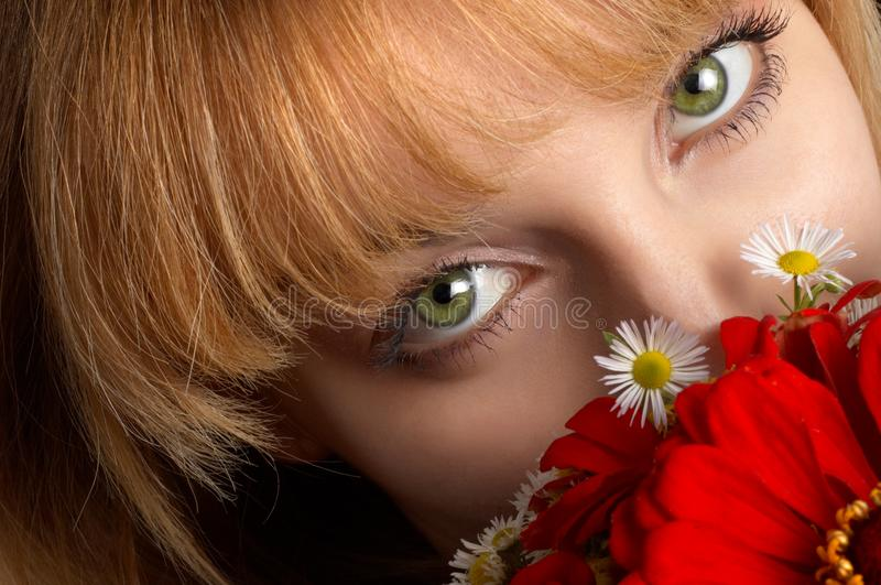 Green eyes and flowers stock photography