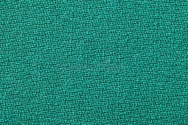 Green fabric background texture. Detail of textile material close-up royalty free stock photo