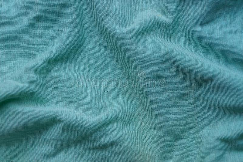 Green fabric texture from a piece of crumpled clothes. Green background of fabric from a piece of crumpled clothes royalty free stock photography