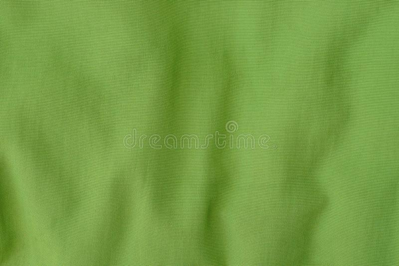 Green fabric texture from a piece of crumpled  clothes stock image