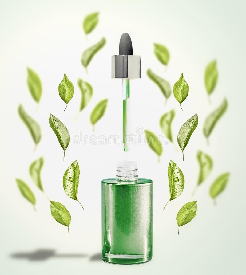 Green facial Serum or oil bottle with pipette and green leaves. Modern skin care and beauty stock image
