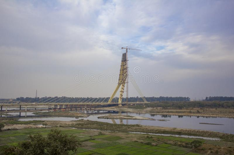 Green farm fields near a cable-stayed bridge under construction and a tower crane over the Yamuna River against a blue sky. royalty free stock images