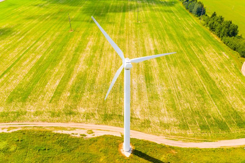 Green farmland concept. Wind turbine in rural area. Aerial landscape royalty free stock images