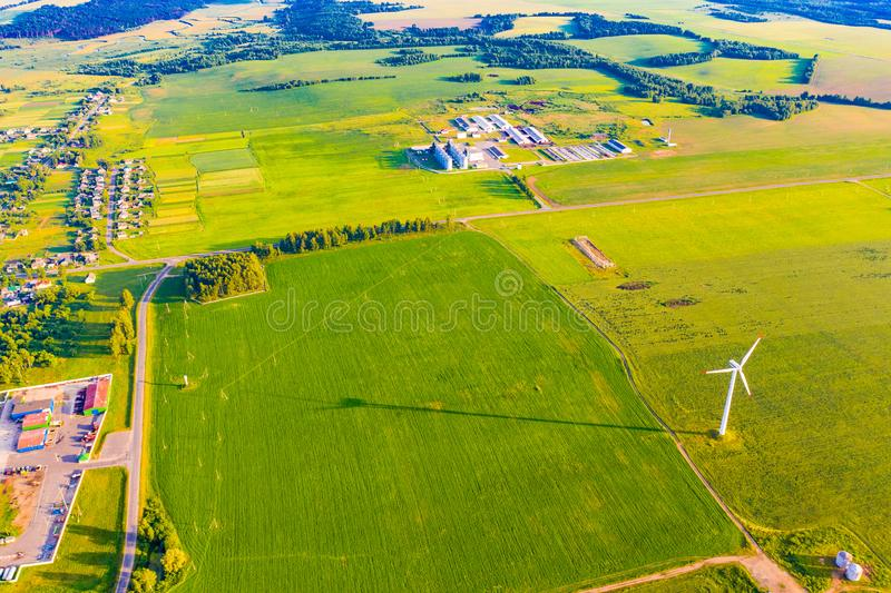 Green farmlands on sunny day, aerial landscape. Alternative energy source concept. Wind turbine in countryside. Green farmlands on sunny day, aerial landscape stock image