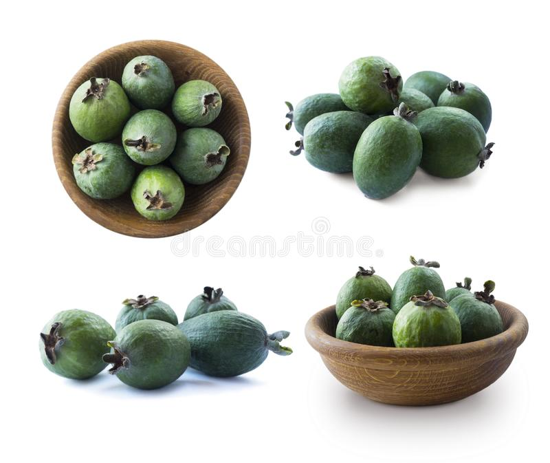 Green feijoa fruits in a wooden bowl isolated on white background. Top view. Fruits from different angles on white. stock photos