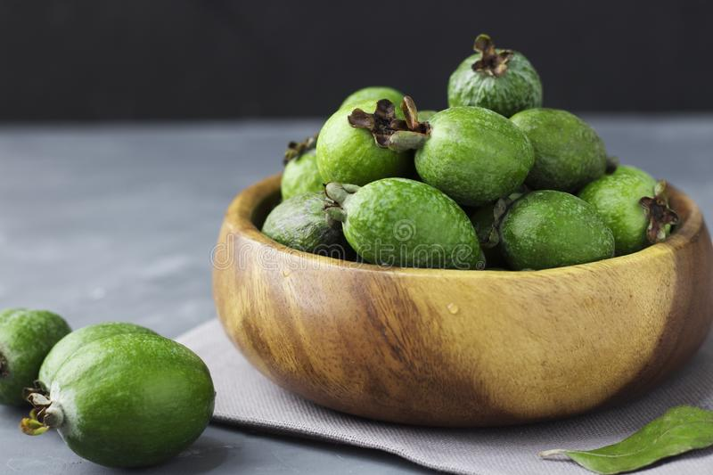 Green feijoa fruits in a wooden plate on a dark background. Tropical fruit feijoa. Set of ripe feijoa fruits. Copy space royalty free stock image