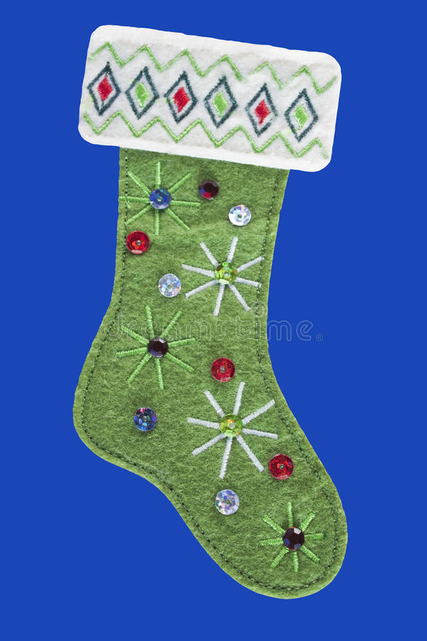 Green felt Christmas Stocking. With embroidery, sequins and isolated on a blue background stock photography