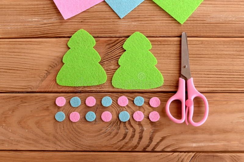 Green felt Christmas tree patterns, pink and blue balls, scissors on wooden background. Master class for kids. Step stock photos