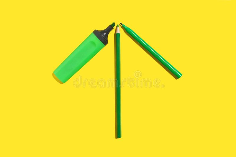 Green felt pen, marker and pencil on a yellow surface royalty free stock image
