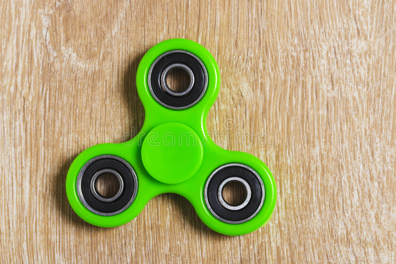 Green fidget spinner toy. On a wooden floor royalty free stock photos