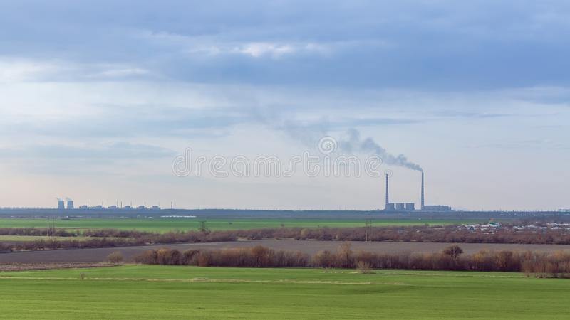 Green field on the background of urban industrial zone stock images