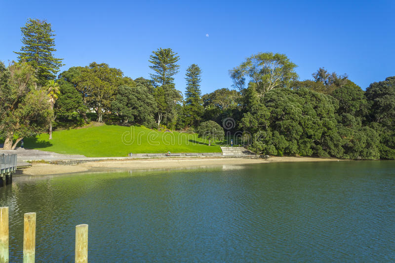 Green Field and Calm Water at Judges Bay Parnell Auckland New Zealand. Nice place for family picnic and relaxing or swimming royalty free stock image