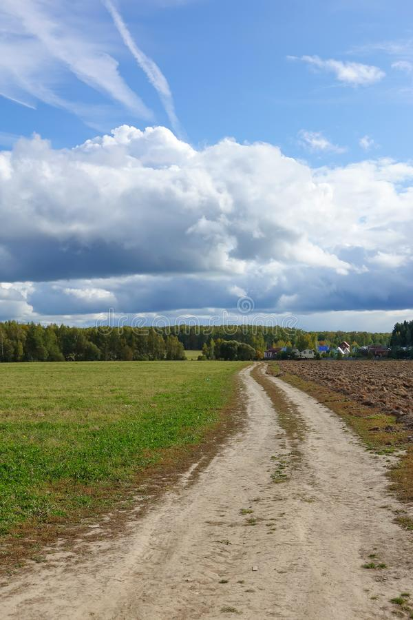 Green field, dirt road. sky with clouds. Beautiful landscape.  royalty free stock images
