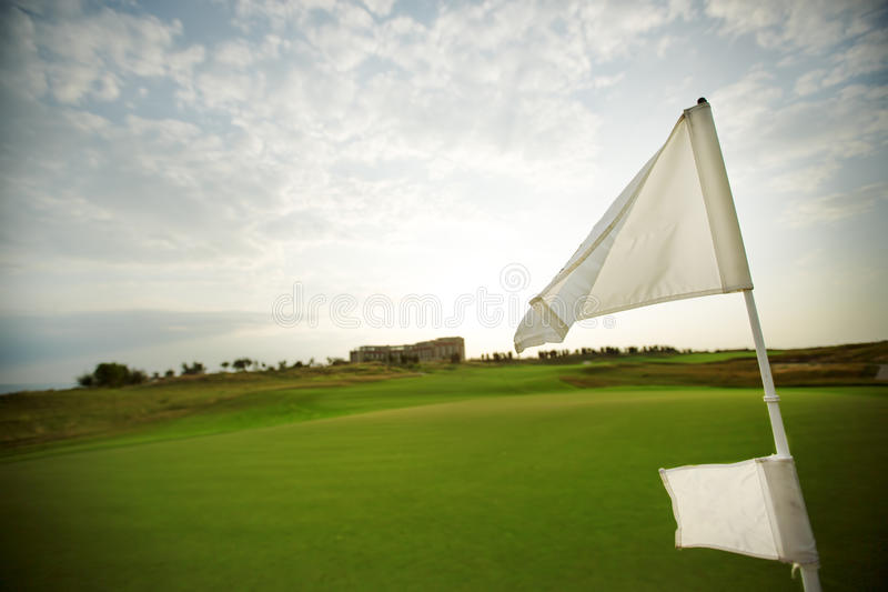 Green field and flag on the golf course stock photography