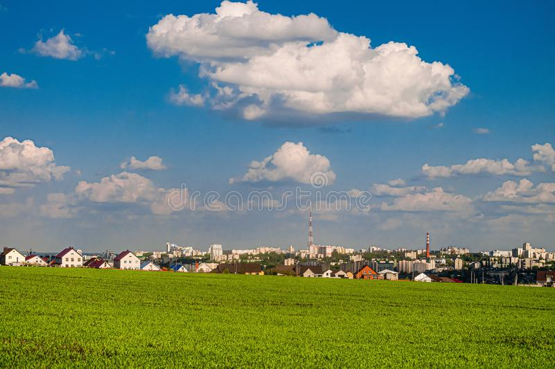 Green field slope and city skyline in the background. Belgorod city, Southwest 2.1 district, Russia.  royalty free stock photography