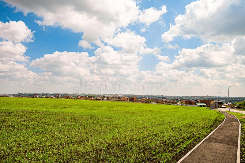 Green field slope and city skyline in the background. Belgorod city, Southwest 2.1 district, Russia.  royalty free stock images