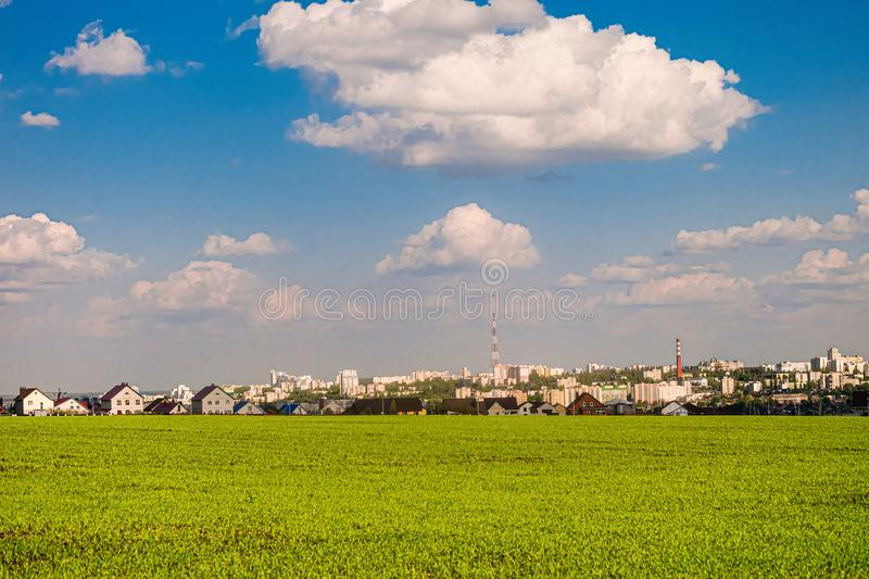 Green field slope and city skyline in the background. Belgorod city, Southwest 2.1 district, Russia.  stock photo