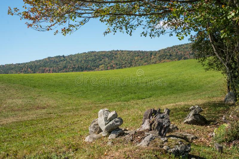 Green Vermont Meadow in Early Autumn. A green field in Vermont in early autumn with foliage just turning royalty free stock images