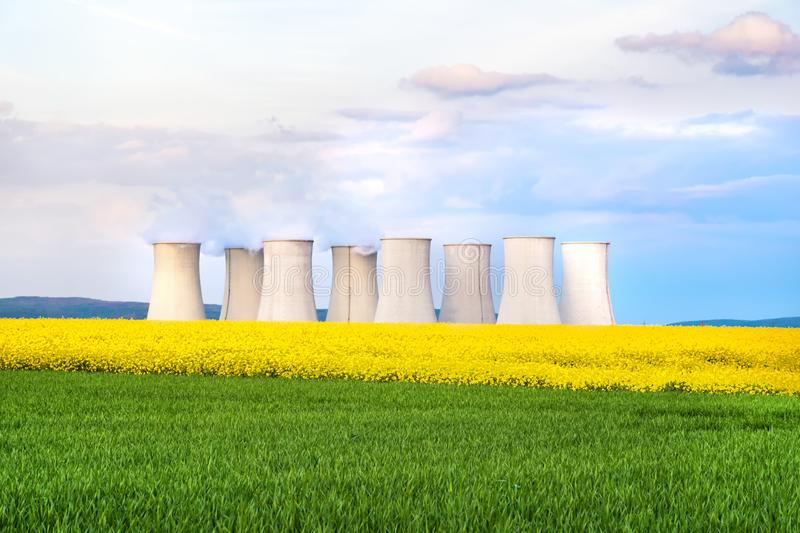 Green field, yellow rapeseed field, cooling towers of nuclear power plant in background royalty free stock photography