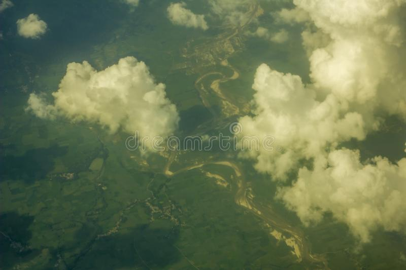 A green fields and forests near the river bed with sandy banks against the background of white clouds. aerial photography stock photo