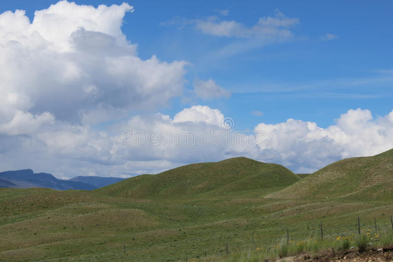 Green fields and hills with mountains in background royalty free stock photography