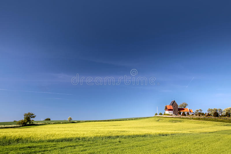 Green fields by the Ruts Kirke church on Bornholm. Denmark royalty free stock image