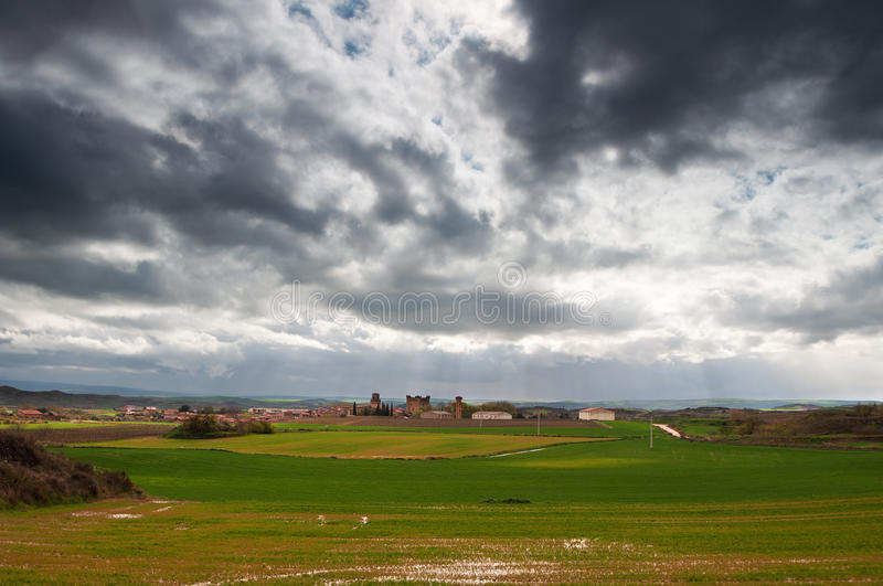 Green fields and a small village with a cloudy sky