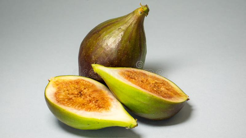 Green figs, one fruit cut in two halves and is a whole fruit on a light gray background. Green figs, one fruit cut in two halves and zhadi is a whole fruit on a royalty free stock images