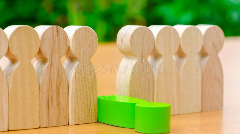 The green figure of a man falls out of the line of people. Concept of employee dismissal and team management in a business company stock photo