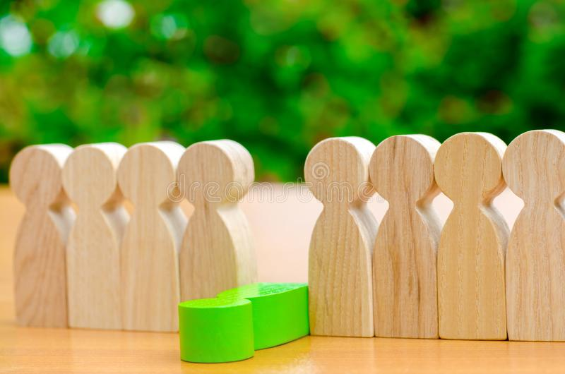 The green figure of a man falls out of the line of people. Concept of employee dismissal and team management in a business company royalty free stock photography