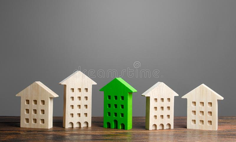 Green figure of a residential building stands out among the rest of the houses. eco-friendly and energy saving stock photos