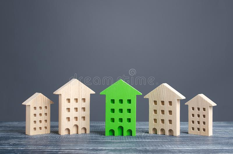 Green figure of a residential building stands out among rest of houses. Zero carbon emissions conservation energy saving. Technologies. Search best option royalty free stock image