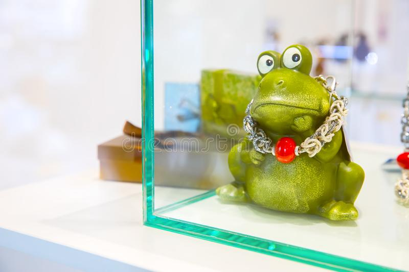 Green figurine in the form of a frog in a shop window with a decoration on the neck. Green statue in the form of a frog in a shop window necklace around his neck royalty free stock photos