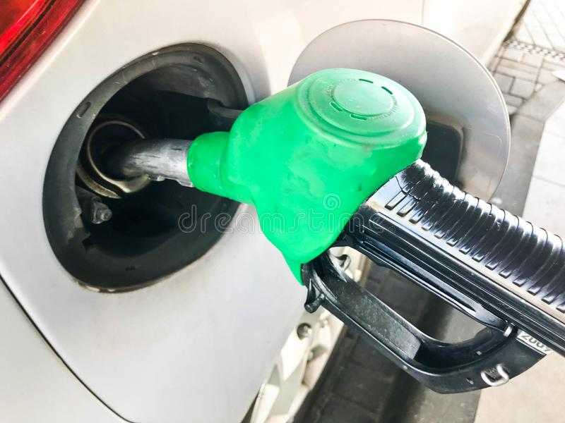 Green filling pistol stuck in the gas tank of a car at a gas station. The process of filling the car with fuel, gasoline, diesel stock photo