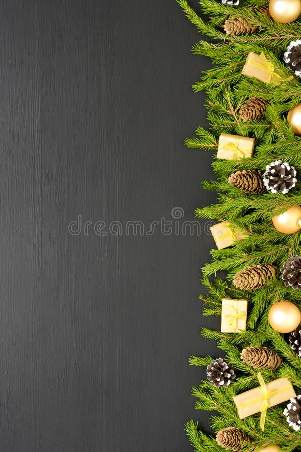 Green fir branches with cones and decorates on black wooden desk. Christmas and New Year border frame. Space for text. Border made of fir branches with cones and stock photography