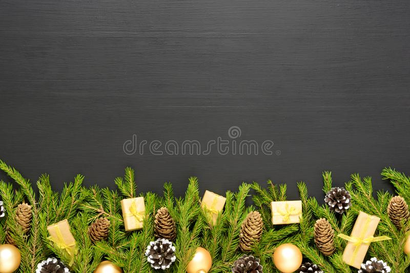 Green fir branches with cones and decorates on black wooden desk. Christmas and New Year border frame. Space for text. Border made of fir branches with cones and stock images